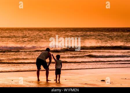 A father and his young son enjoying the beautiful sunset over Fistral Beach in Newquay in Cornwall. - Stock Photo