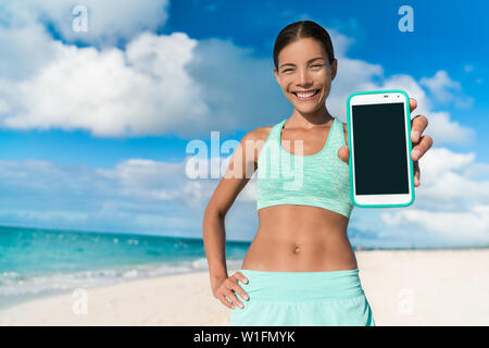 Asian runner girl using smartphone fitness app showing touchscreen for text copyspace. Happy athlete woman showing screen for weight loss progress following online video running workout on beach. - Stock Photo