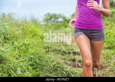 Healthy active woman runner running in outdoor grass nature park trail path. Midsection lower body of girl athlete training cardio. Feminine health care issues: menstrual period pain, stomach problem. - Stock Photo