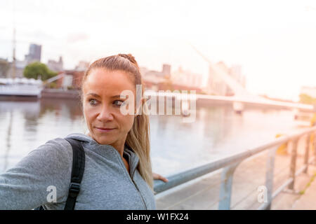 An athletic woman in a grey sweater standing next to the bridge railing. - Stock Photo
