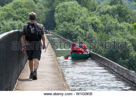 A walker cathces up to a family in a canoe as they try to paddle over the Pontcysyllte Aqueduct in Wales in bright summer sunshine. - Stock Photo