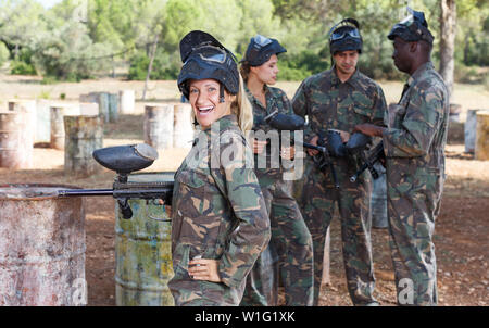 Portrait of happy female paintball player with marker gun ready for game outdoors - Stock Photo