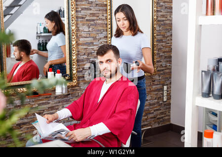 Cheerful pleasant positive  woman professional hairdresser cut male's hair in hairdressing salon - Stock Photo