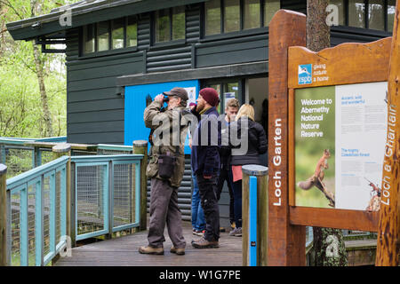 Visitors watching birds at RSPB Loch Garten Osprey Centre in Abernethy Forest Nature Reserve in Cairngorms National Park. Strathspey Scotland UK - Stock Photo