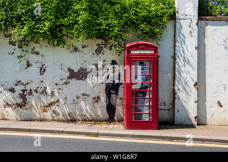 Banksy-style artwork of Edward Elgar in an old Telephone Box below the Rose Garden in Great Malvern, Worcestershire, England - Stock Photo