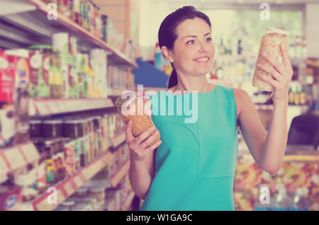 Woman readig label on glass jar of beans in the supermarket - Stock Photo
