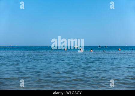 People swimming and playing in the shallow sea water at Le Grau d'Agde Agde, France - Stock Photo