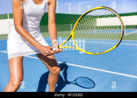Midsection of tennis player woman ready playing game on blue hard court outdoor in position holding racket wearing white dress skirt. Female athlete sporty girl for summer sports activity course. - Stock Photo