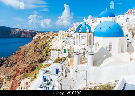 Greece famous touristic travel destination Santorini greek island. Three blue domes. Popular summer luxury vacation Europe cruise stop. Streets of European white village with the mediterranean sea. - Stock Photo