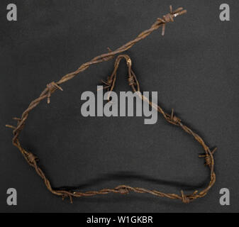 Very old folded and rusty barbed wire fence on black background - Stock Photo