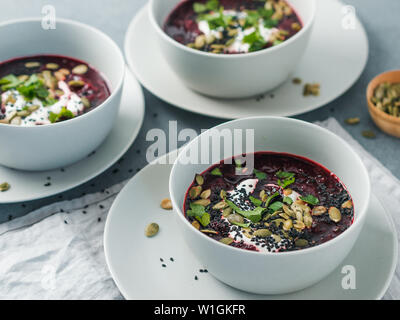 Ideas and recipes for healthy soup - Beetroot and ginger soup puree. Clean eating, detox, vegetarian diet concept. Plates with perfect beet soup, dressed pepitas, sesame and parsley - Stock Photo