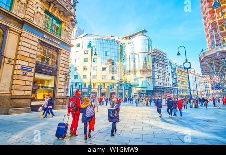 VIENNA, AUSTRIA - FEBRUARY 18, 2019: Tourists walk along central streets in Vienna enjoying magnificent architecture of surrounding edifices and look - Stock Photo