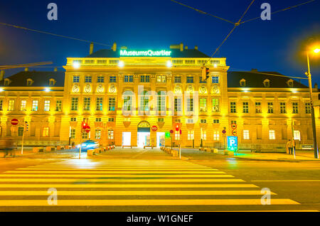 VIENNA, AUSTRIA - FEBRUARY 18, 2019: The evening Ringstrasse road with a view on the facade of Museums Quartier Baroque building in bright evening lig - Stock Photo