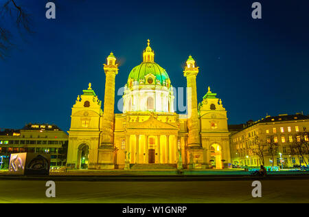 VIENNA, AUSTRIA - FEBRUARY 18, 2019: The bright illuminated Karlskirche (Charles Church), that is one of the most unufual churches in city with two ca - Stock Photo
