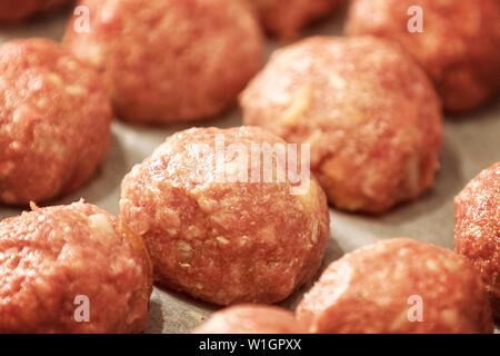 Uncooked dumplings on tray. Fresh minced meat in the form of balls with pepper, salt. Close up and soft focus - Stock Photo