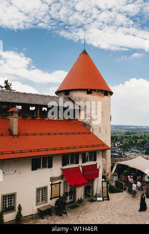 Bled, Slovenia - September, 8 2018: View of the The Bled Castle courtyard, tower and castle buildings with cafes and souvenir shops, located on the ba - Stock Photo