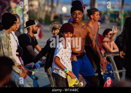 Young skaters embracing in the skate park in Venice Beach, Los Angeles, California, USA - Stock Photo