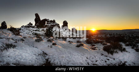 The sun sets on Turret Arch in Arches National Park as freshly fallen snow forms a pattern on the desert floor. (c) 2012 Tom Kelly - Stock Photo