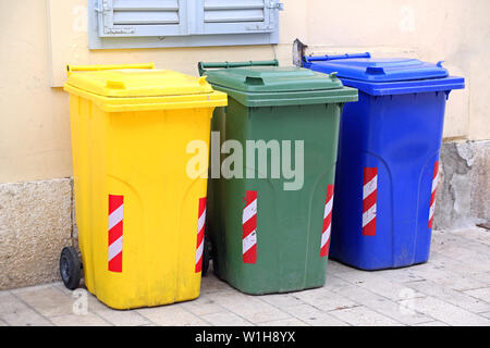 Three Recycling and Sorting Plastic Trash Wheelie Bins - Stock Photo