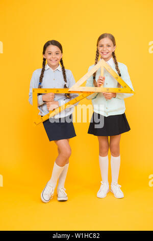 Move from theory to practice. Excellent pupils. Secondary school. Schoolgirls tidy appearance school uniform hold big rulers for geometry school lesson. Kids cute students study math. Knowledge day. - Stock Photo