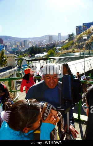 La Paz, Bolivia 2nd July 2019: An Aymara boy observes a partial eclipse of the sun through a telescope at an eclipse watching event near the city centre. In La Paz the eclipse lasted for about 2 hours 10 minutes with about 55% coverage at its maximum. The skyscraper right of centre is the new Presidential Palace / Casa Grande del Pueblo. - Stock Photo