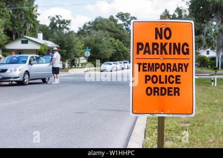 Mount Dora Florida Mt. Annual Craft Fair temporary sign police order warning no parking street parked car man - Stock Photo