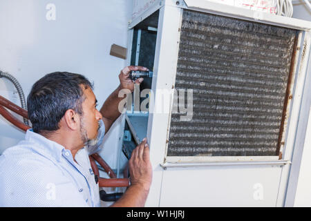 Miami Beach Florida Presidential Condominiums central air conditioner AC conditioning repair repairman mechanic job Hispanic man - Stock Photo