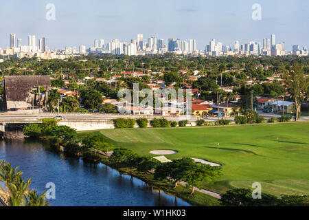 Miami Florida canal downtown skyline buildings panoramic urban golf course trees green houses - Stock Photo