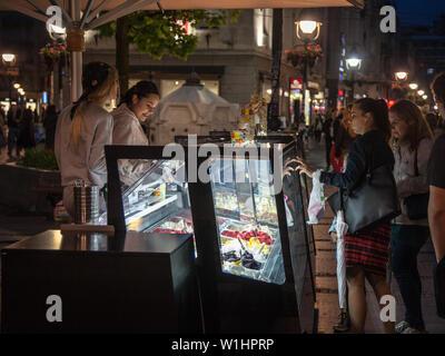 BELGRADE, SERBIA - JUNE 26, 2018: Ice cream parlour selling italian gelato to girls in a pedestrian street of Belgrade, Serbia, at night, zith a zide - Stock Photo