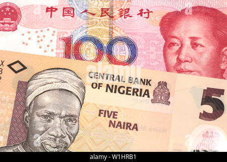 An orange five naira note from Nigeria with a red, one hundred yuan renminbi note from China close up in macro - Stock Photo