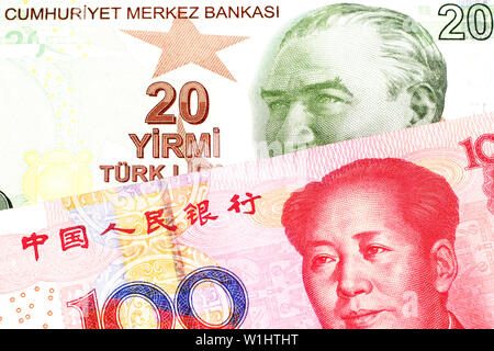 A close up image of a red, yellow and green twenty Turkish lira bank note with a red one hundred Chinese renminbi bill in macro - Stock Photo