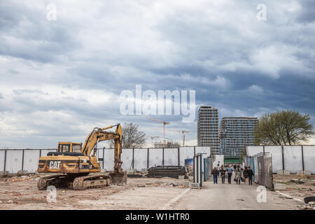 BELGRADE, SERBIA - MARCH 31, 2018: people passing by a Cat excavator in the construction site of Beograd na Vodi, a controversed Skyscraper business p - Stock Photo