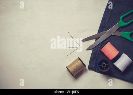Sewing tools and equipment on white wooden floor. Top view and copy space for text. Concept of tailor or fashion designer.