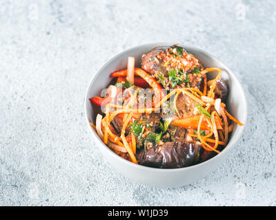 Salad of pickled eggplant, carrot, onion, sweet pepper in bowl on gray cement background. Fermented food. Preserved vegetables. Copy space for text. - Stock Photo