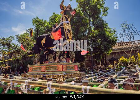 Ubud, Bali, Indonesia - April 22, 2019 : Royal cremation ceremony prepation. Balinese hindus religion procession. Bade and Lembu Black Bull symbol of - Stock Photo