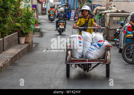 Bangkok, Thailand - April 12, 2019: Young boy transporting goods on an old motorcar on the streets of Bangkok - Stock Photo