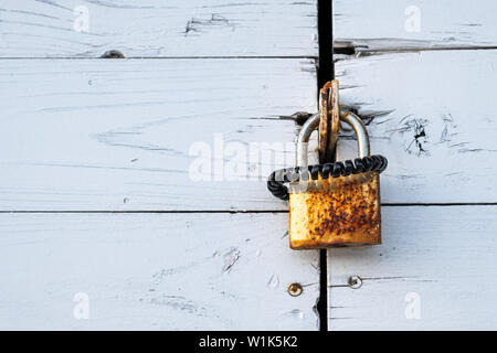 rusty lock with black scrunchy hanging on a wooden door in the evening sun - Stock Photo