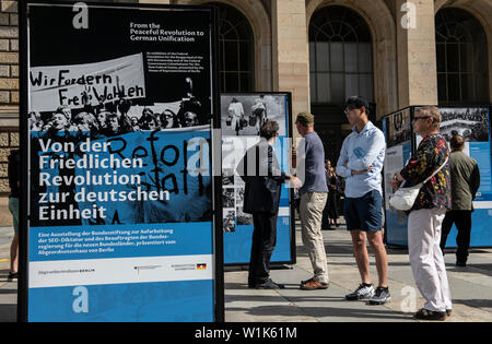 Berlin, Germany. 03rd July, 2019. People are standing in front of information boards at the House of Representatives. They are part of the new open-air exhibition 'From the Peaceful Revolution to German Unity', organized by the Bundesstiftung zur Aufarbeitung der SED-Diktatur. The occasion for the presentation is the upcoming 30th anniversary of the fall of the Berlin Wall. Credit: Paul Zinken/dpa/Alamy Live News - Stock Photo