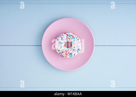 One white donut or doughnut in a pink plate on a pastel blue wooden table background. Top view. - Stock Photo