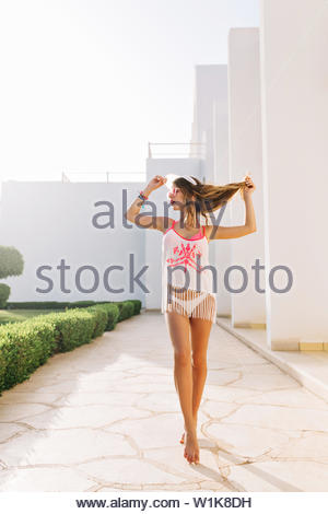 Full-length portrait of dancing girl with tanned skin and red lips looking away, holding her long hair. Gorgeous slim young woman in fringe shirt standing on tip-toes, posing after rest on beach - Stock Photo