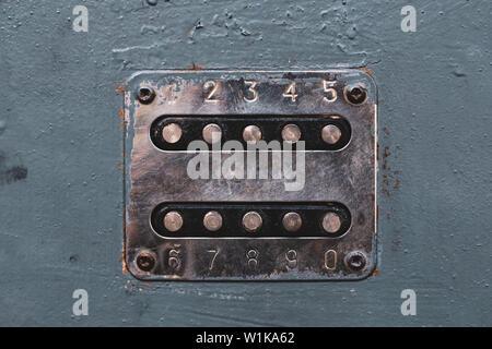 Number buttons to unlock the door lock. Panel with numbers on the old metal door. Unlocker buttons on metal door. Steel numeric keyboard - Stock Photo