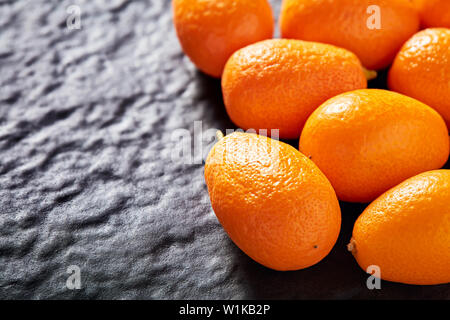 Heap of kumquat on black textured stone background with copy space. Close up macro view.