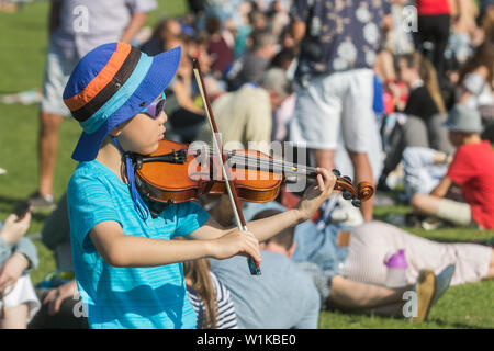 Wimbledon London, UK. 3rd July 2019.  5 year old Jimmy plays the violin  while queueing for tickets in the sunshine on day three of the Wimbledon Championships. Credit: amer ghazzal/Alamy Live News - Stock Photo