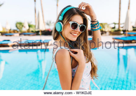 Close-up portrait of tunned girl with shy smile, walking by blue pool in big bright headphones. Amazing young woman in white tank-top listening music, while resting on exotic summer resort - Stock Photo