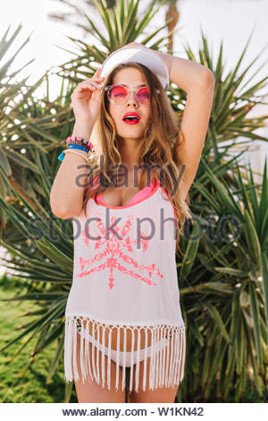 Cute girl with dreamy face expression posing with hands up during walk in palm tree garden on resort. Gorgeous young woman in pink swimsuit and fringe shirt spending time outside enjoying southern sun - Stock Photo