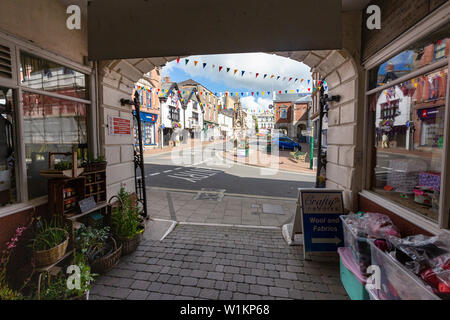 View of The Square, (Town Centre), Town Hall and Clock Tower from the Main Entrance to the Great Torrington Pannier Market. - Stock Photo