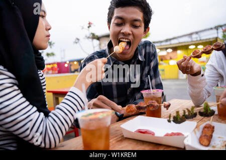 Group of young friends enjoying meal in outdoor - Stock Photo