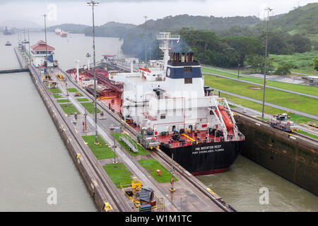 Panama Canal / Panama - May 18.2007: View on the big ship sailing through the Panama Canal. Vessel slowly moving in the locks attached to the cart - Stock Photo