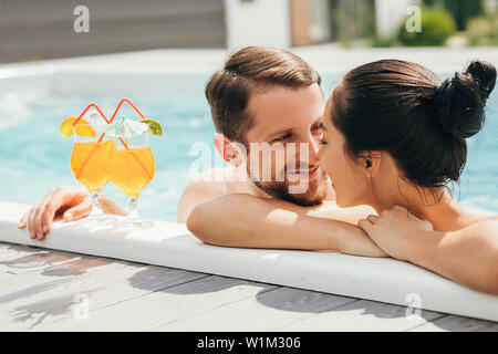 man and a woman look lovingly at each other while in the pool. Goodbye work, hi summer vacation-swimming and tanning - Stock Photo