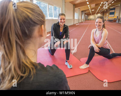 Young women practicing yoga in athletics hall on tartan track, Offenburg, Baden-Württemberg, Germany - Stock Photo